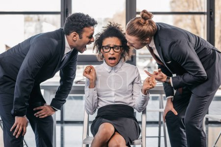 businessmen screaming on businesswoman in office