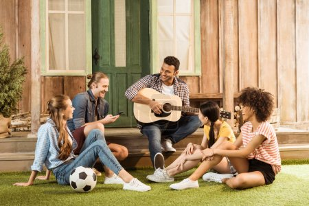 Photo for Multiethnic people spending time together, smiling man playing guitar while other friends listening - Royalty Free Image