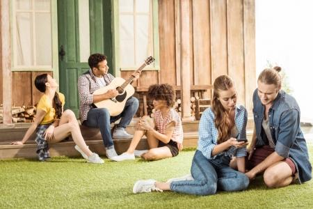 Photo for Young couple sitting and using smartphone while their friends playing guitar behind - Royalty Free Image