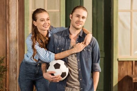 Couple holding soccer ball