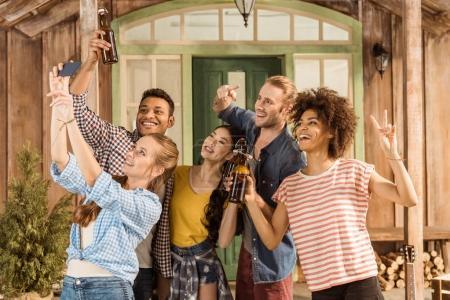 Foto de Grupo multiétnico de amigos con cerveza mostrando el signo de la paz y tomar selfie - Imagen libre de derechos