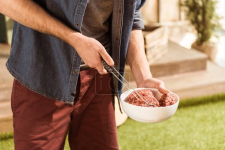 Photo for Cropped view of man preparing raw meat for burgers outdoors - Royalty Free Image