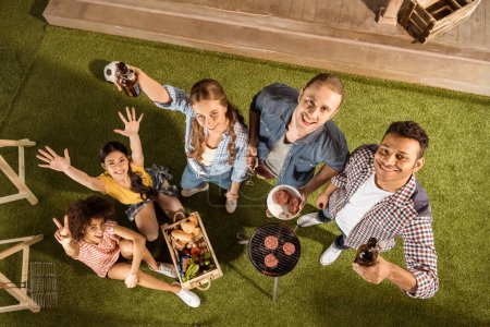 Photo for High angle view of happy young friends grilling burgers and drinking beer - Royalty Free Image