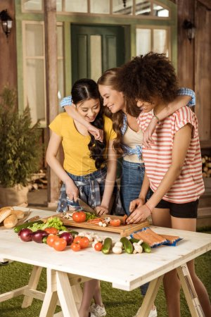Young women cutting vegetables