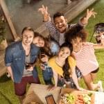 High angle view of happy young friends smiling at camera at picnic