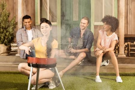 Woman preparing barbecue while friends sitting