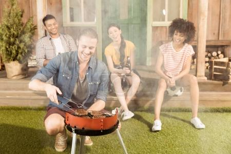 man preparing barbecue while friends sitting