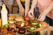 woman preparing hamburgers on kitchen board