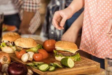 Woman preparing hamburgers on kitchen board
