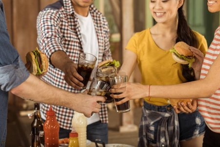 Friends clinking with glasses of cola at picnic