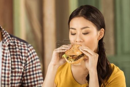 junge asiatische Mädchen essen Burger