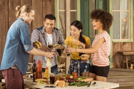 Multiethnic friends clinking with glasses at picnic