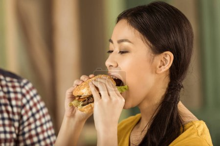 Young asian girl eating burger