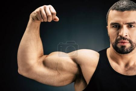 Photo for Selective focus of strong man showing muscles isolated on black - Royalty Free Image