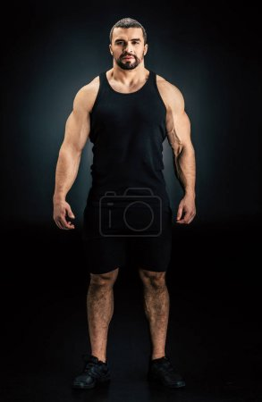 Photo for Handsome athletic man looking at camera isolated on black - Royalty Free Image