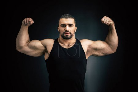 Photo for Portrait of strong man showing muscles isolated on black - Royalty Free Image