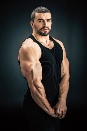 Photo for Portrait of strong man showing muscles and looking at camera isolated on black - Royalty Free Image