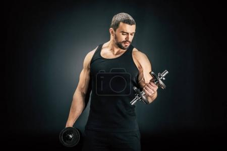Photo for Portrait of sportive man pumping muscles with dumbbells in hands isolated on black - Royalty Free Image