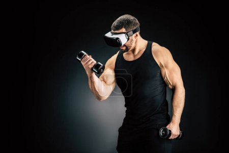 Photo for Fit man exercising with dumbbells in vr headset isolated on black - Royalty Free Image