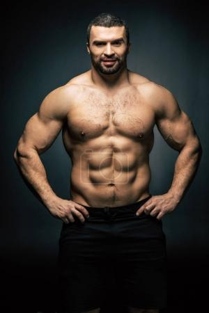 Photo for Portrait of shirtless sportive man standing akimbo isolated on black - Royalty Free Image
