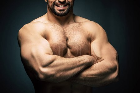 Photo for Cropped shot of shirtless sportive man with arms crossed showing muscles isolated on black - Royalty Free Image