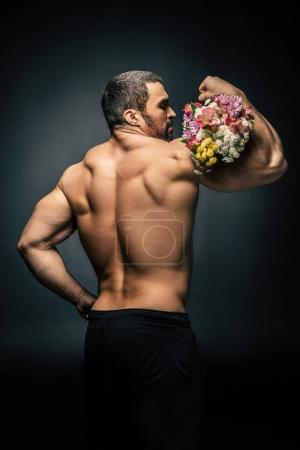 sportive man with bouquet of flowers