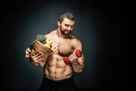Photo for Portrait of shirtless athletic man with healthy food looking at dumbbell in hand isolated on black - Royalty Free Image