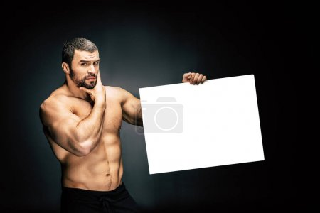 Photo for Portrait of shirtless athletic man with blank banner in hand looking at camera isolated on black - Royalty Free Image