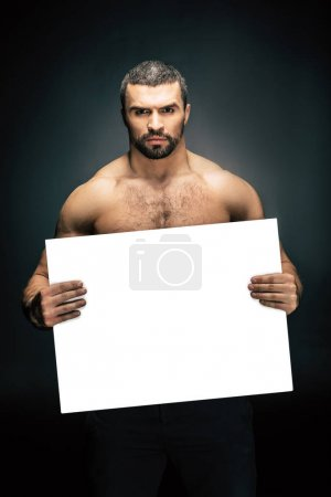 Photo for Portrait of shirtless athletic man holding blank banner in hands isolated on black - Royalty Free Image