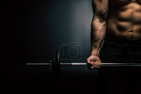 Photo for Partial view of athletic man weightlifting isolated on black - Royalty Free Image