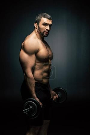 Photo for Side view of shirtless athletic man weightlifting isolated on black - Royalty Free Image