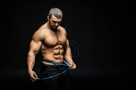 Sportive man with measuring tape