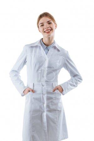 Photo pour Jeune femme souriante chimiste en manteau blanc, isolée sur blanc - image libre de droit
