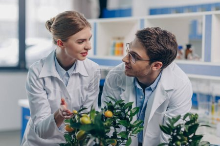 Photo for Happy biologists in white coats with lemon plants in laboratory - Royalty Free Image