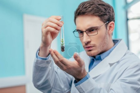 biologist with plant in flask