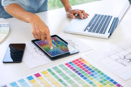 Photo for Creative creativity graphic designer working with graphics tablet,laptop and smart phone, colour chart at workplace on wooden desk , colour ideas style concept. - Royalty Free Image