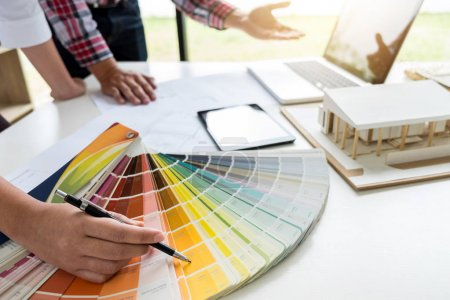 Photo for Two young women interior design or graphic designer working on project of architecture drawing with work tools and color swatches, colour chart in digital tablet at workplace. - Royalty Free Image