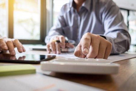 Photo pour Équipe d'affaires deux collègues de direction discutant et analysant travailler Investissement financier sur calculatrice avec calculer sur tablette Analyser la croissance des affaires et du marché sur le graphique de données de documents financiers. - image libre de droit