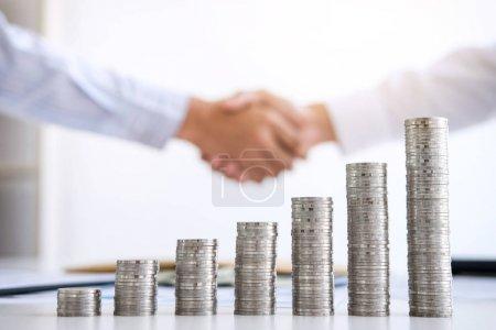 Photo pour Poignée de main d'affaires pour la collaboration, indices financiers boursiers et croissance empilant pièces de monnaie et coûts financiers judicieusement et soigneusement, concept d'investissement et d'épargne . - image libre de droit
