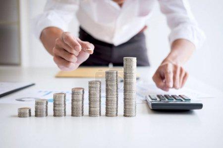 Photo pour Comptable ou banquier d'affaires, homme d'affaires calculer et analyser avec des indices financiers boursiers et mettre la croissance empilant pièces et coûts financiers judicieusement et soigneusement, concept d'investissement et d'épargne . - image libre de droit