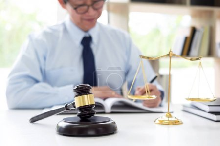 Judge gavel with scales of justice, male lawyers w...