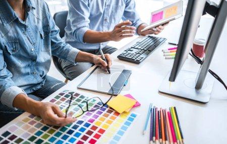 Zwei Kollegen kreative Grafik-Designer arbeiten an Farbauswahl und Farbmuster, Zeichnung auf Grafik-Tablet am Arbeitsplatz mit Werkzeugen und Zubehör.