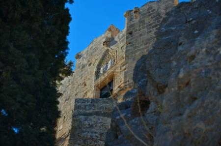View of a rock wall with walls and a medieval castle enlightened by the sun through the trees, under a blue sky