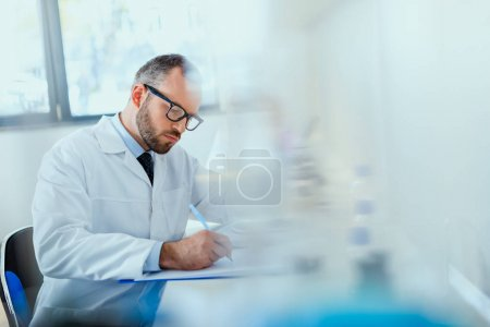Photo for Young doctor in uniform working at testing laboratory at clinic, doctor concept - Royalty Free Image