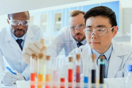 Photo for Multiethnic group of scientists in protective eyeglasses working together in chemical laboratory - Royalty Free Image