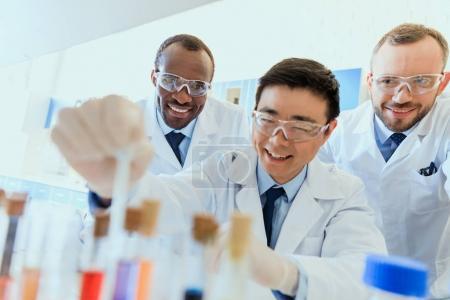 Photo pour Groupe de scientifiques souriants en lunettes de protection travaillant ensemble en laboratoire chimique - image libre de droit
