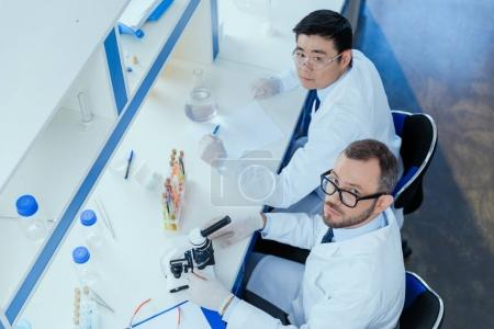 Photo for High angle view of chemists in eyeglasses and lab coats working together in chemical laboratory - Royalty Free Image