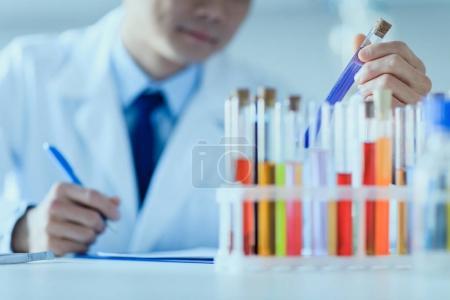 Photo pour Plan recadré d'un scientifique en blouse de laboratoire tenant une éprouvette et prenant des notes, concept de chercheur de laboratoire - image libre de droit