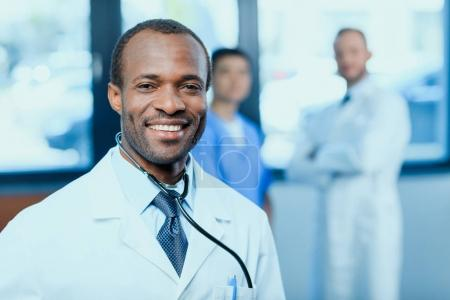 Photo for Portrait of smiling doctor with stethoscope with colleagues behind in clinic - Royalty Free Image
