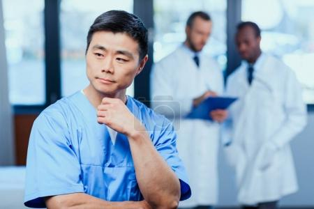 Photo for Portrait of pensive doctor in medical uniform with collegues behind in clinic - Royalty Free Image